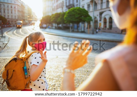 Life during covid-19 pandemic. elegant mother and child with masks and yellow backpack say goodbye before going to school outdoors. Foto stock ©