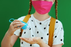 Life during covid-19 pandemic. modern school girl in white polka dot blouse with yellow backpack and pink mask disinfecting hands with an antibacterial agent against chalkboard green background.