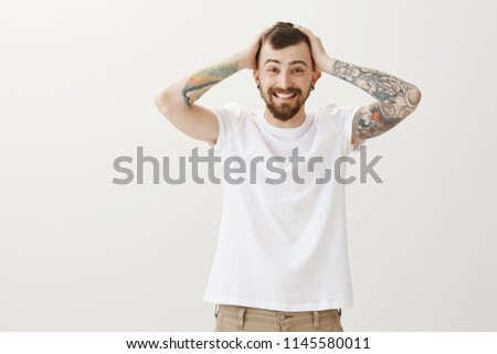 Life filled with happiness. Indoor shot of carefree friendly loving boyfriend with beautiful smile and tattoos, holding hands on head and grinning, being upbeat after hearing great news over gray wall