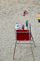 life guard on duty sitting in a tower watching beach goers