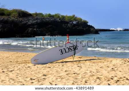 Life guard surf board sits ready for action.  The word Rescue is painted in black on the board.