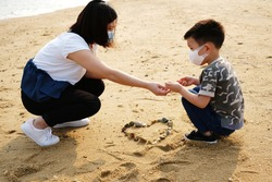 Life in coronavirus COVID-19. An asian boy wearing a mask to play rocks with mother in a beach.