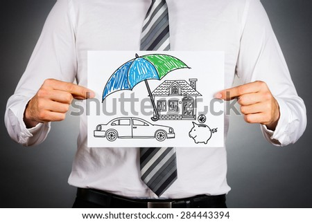 Life insurance concept. Businessman holding paper with drawing of a house, car and money symbols under the umbrella.