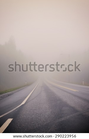 Life is a journey as they say. An image of a very foggy road in autumn. Image has a strong vintage effect.