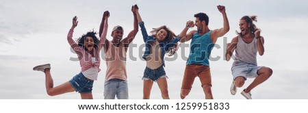 Life is better with friends. Full length of young people in casual wear smiling and gesturing while jumping on the pier #1259951833