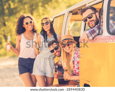 Life is brighter when friends are near. Group of cheerful young people enjoying time together while sitting and standing near their retro minivan
