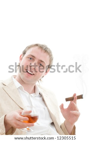 Life is good, if you rest with pleasure! Young successful businessman leans back in chair with glass of cognac and smoking a good cigar. Isolated on white.