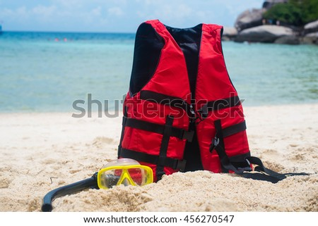 Life jacket and a mask for snorkeling on the beach #456270547