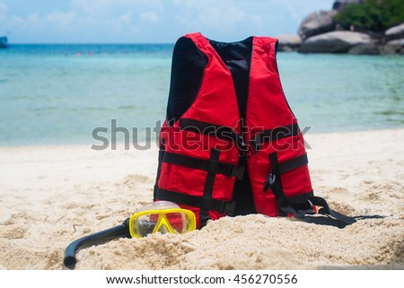 Life jacket and a mask for snorkeling on the beach #456270556