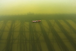 Life of fisherman on wooden boat in Songkalia River, Famous travel destination in Sangkhlaburi Kanchanaburi, Thailand