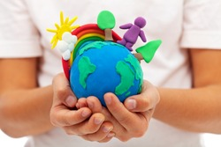 Life on earth - environment and ecology concept with clay earth globe in child hands