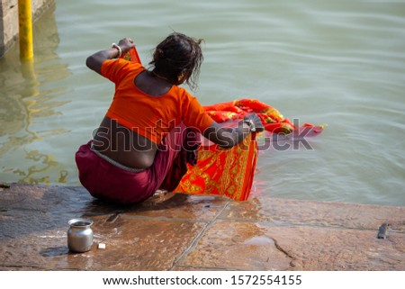 Life on the Ganges: Low caste untouchable indian woman washing a #1572554155