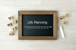 Life planning scale on blackboard and wooden blocks with house events pictogram