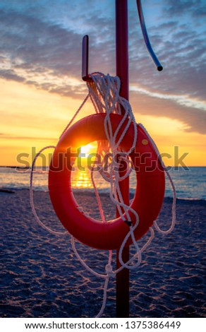 LIFE PRESERVER/BUOY AT BEACH - Beautiful shot of life preserver on pole, with colorful sunset in background. First aid survival equipment/gear to save lives in emergency. Toronto, Ontario, Canada.