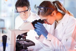 Life scientists researching in laboratory. Female young scientist and her post doctoral supervisor microscoping in their working environment. Health care and biotechnology.