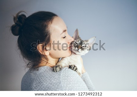 Life style photo of a casual dressed female who  is holding and petting and kissing cute Devon Rex cat. Kitten enjoys being in girls arms. Selective focus.