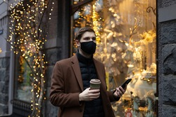 Life style portrait of a man walking to the office. Young male wearing black face mask. Mobile phone in hand. Street style portrait wearing winter clothes. Christmas shop light in the background