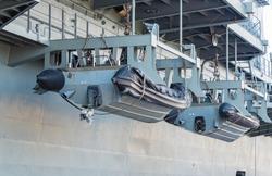 Lifeboat hanging on battle ship at port.