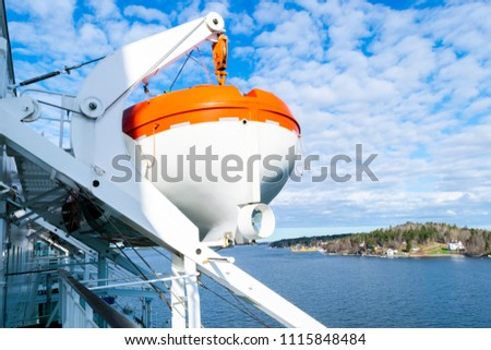 Lifeboats, decks and cabins on the side of cruiseship. Wing of running bridge of cruise liner. White cruise ship on a blue sky with radar and navigation system. Captain's cabin.