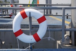 Lifebuoy hanging on metal fence at public pier for rescue when emergency. Pier, metal pillar, river background. Concept of safe travels, lifebuoy, safety equipment.