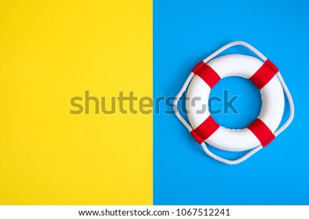 Lifebuoy on a yellow and blue background with blank space for text. Top view travel or vacation concept. Summer background. Flat lay photo, top view ストックフォト ©