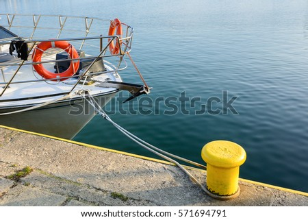 Lifebuoy on board white boat and mooring bollard in port of Wladyslawowo. Poland.