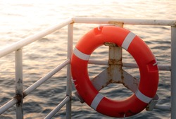 Lifebuoy or life ring orange on the ship with backdrop of the sea landscape. Safety equipment. High quality stock photo image of obligatory ship equipment, personal flotation device prevent drowning