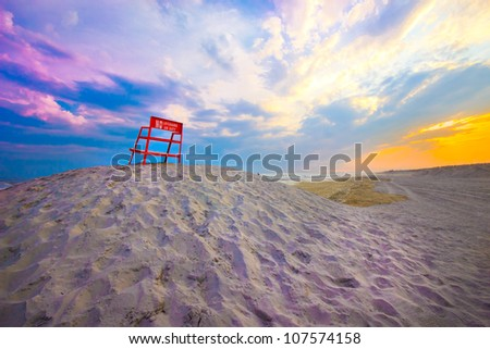 Lifeguard chair on sand dune as sunsets over beach