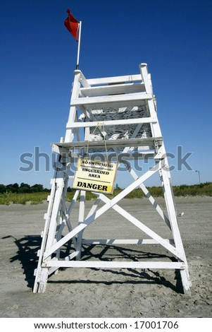 lifeguard chair with sign indicating danger
