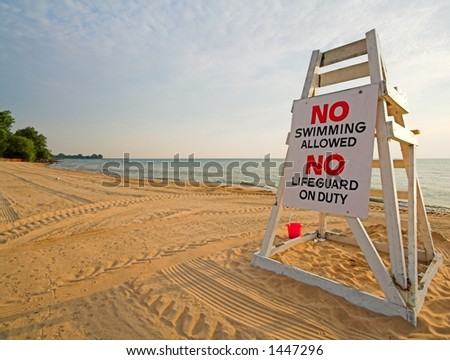 lifeguard chair with sign saying no swimming - stock photo