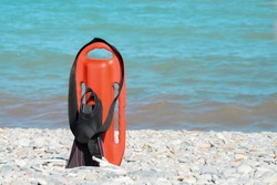 Lifeguard equipment on the water, red plastic boat with hand grips and rubber fins, cooked on a stone seaside in the sun, nobody, close-up
