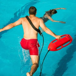 Lifeguard jumping into a swimming pool to rescue drowning victim
