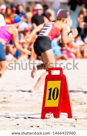 lifeguard lifesafer championships with woman in race course competition with officials and spectators