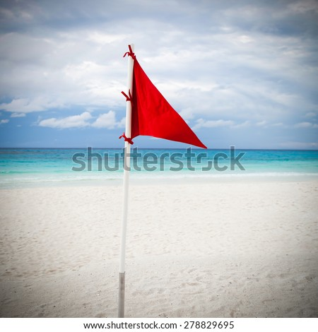 Lifeguard red flag at caribbean beach in bad weather