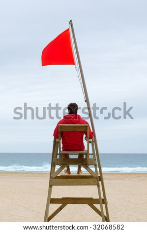 Lifeguard sitting in his chair watching the sea - stock photo