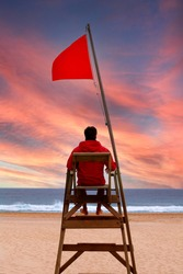 Lifeguard sitting on a high chair looking at the sea. Red flag
