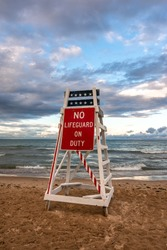 Lifeguard stand with no lifeguard on duty as the sun sets on lake Michigan.  Lighthouse beach, Evanston, Illinois