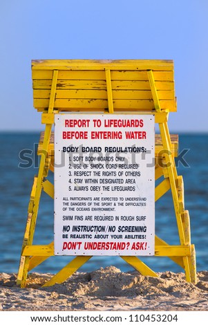 Lifeguard tower at a beach with regulations sign.