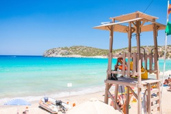 Lifeguard tower at beautiful blue beach. Greece, Crete, Voulisma beach. Lifeguard cabin on the beach. Mediterranean sea.