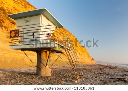 Lifeguard tower in front of a large cliff with the glow of the evening sun.
