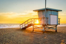 Lifeguard Tower on the Beach at Sunset with the Sun shining through.