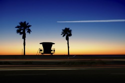 Lifeguard Tower with Palm trees at sunset. Airplane's contrail, flying across the orange, blue sky and cars in motion.