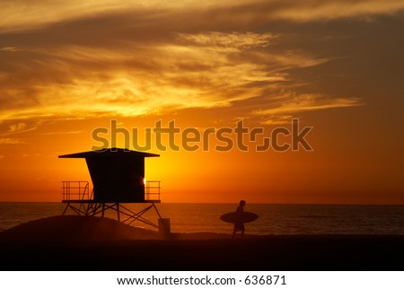 Lifeguard tower with setting sun on the horizon and the silhouette of the surfer