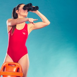 Lifeguard with rescue tube buoy. Woman supervising swimming pool water looking through binoculars. Accident prevention and rescue.