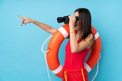 Lifeguard woman over isolated blue background with lifeguard equipment and with binoculars while pointing far