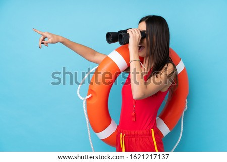 Lifeguard woman over isolated blue background with lifeguard equipment and with binoculars while pointing far Foto stock ©