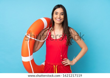 Lifeguard woman over isolated blue background with lifeguard equipment and with happy expression Foto stock ©
