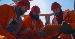 Lifeguards using tablet studying map sitting in boat. Professional rescue service team inside hovercraft using digital tablet checking area of frozen lake or sea in winter