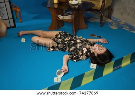 Lifeless brunette in a dressing gown lying on the floor