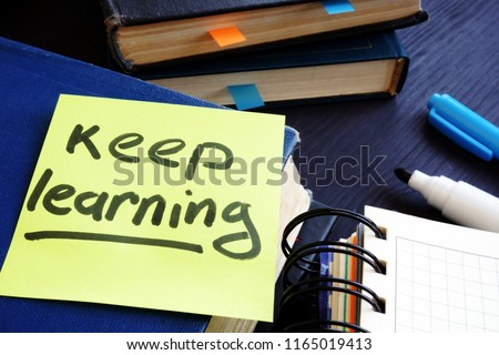 Lifelong learning concept. Book and piece of paper with words keep learning.